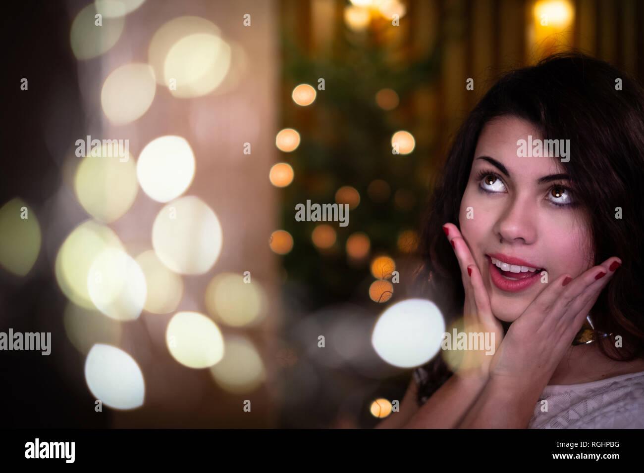 Giovane e bella donna di fronte a albero di Natale cercando nella credenza. Immagini Stock