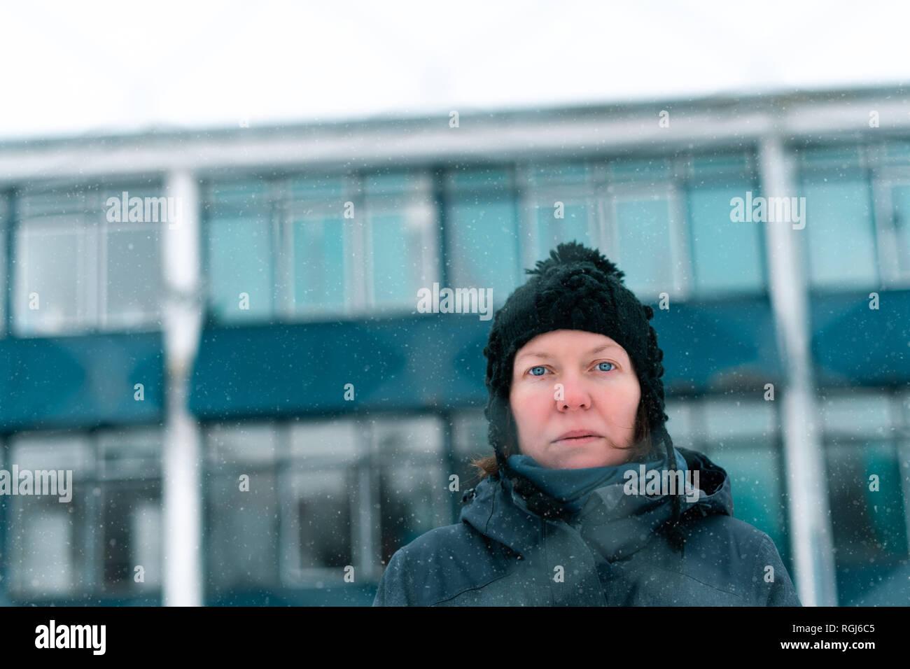 Preoccupato in questione grave donna dietro a catena collegamento recinto  come ostacolo sulla fredda giornata invernale 414bc5370687