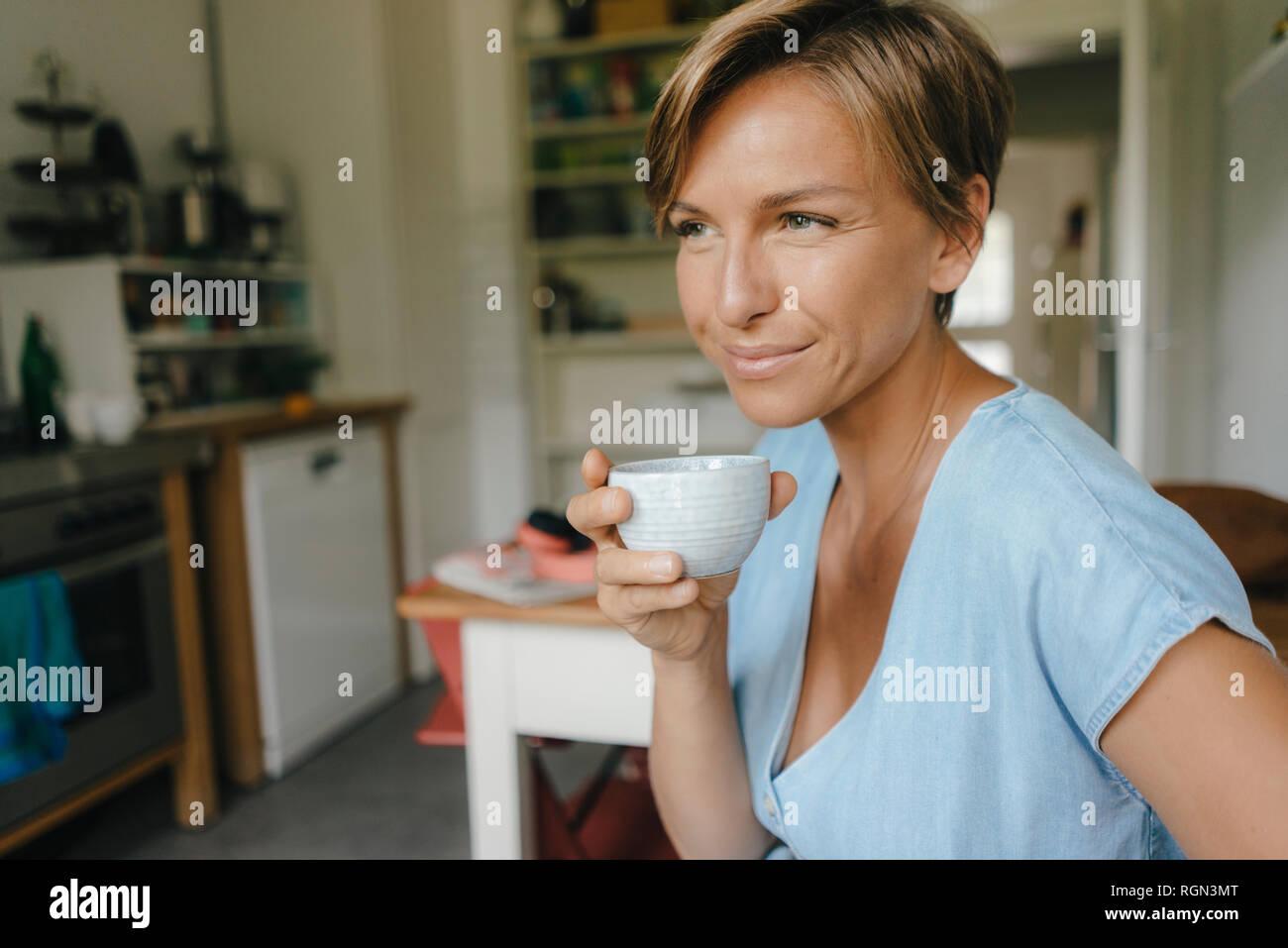 Donna sorridente a casa a bere tazza di caffè Foto Stock