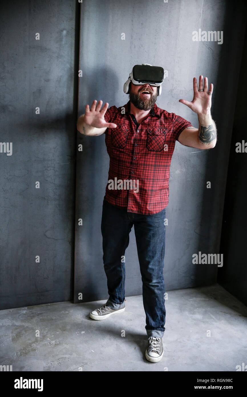 Eccitato uomo barbuto che indossa gli occhiali VR Immagini Stock