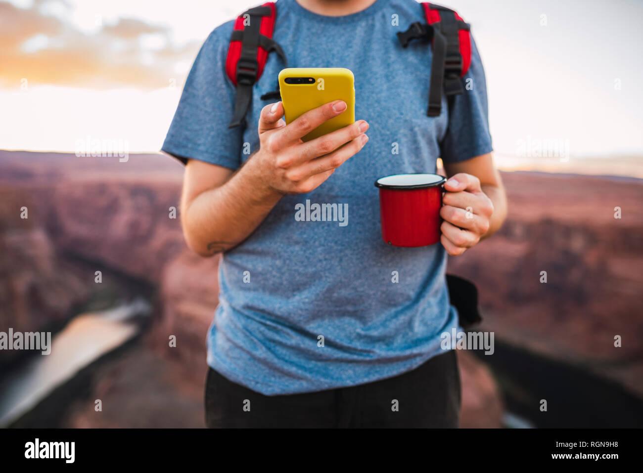 Giovane Azienda red cup e utilizza lo smartphone Foto Stock