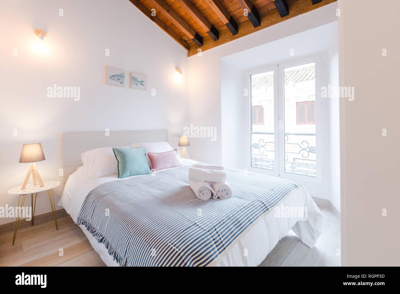 Luce confortevole camera con letto grande e lampade vicino alla finestra nella casa moderna Immagini Stock