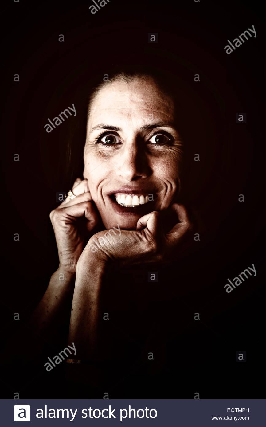 Ritratto oscuro di sorridere donna di mezza età Immagini Stock