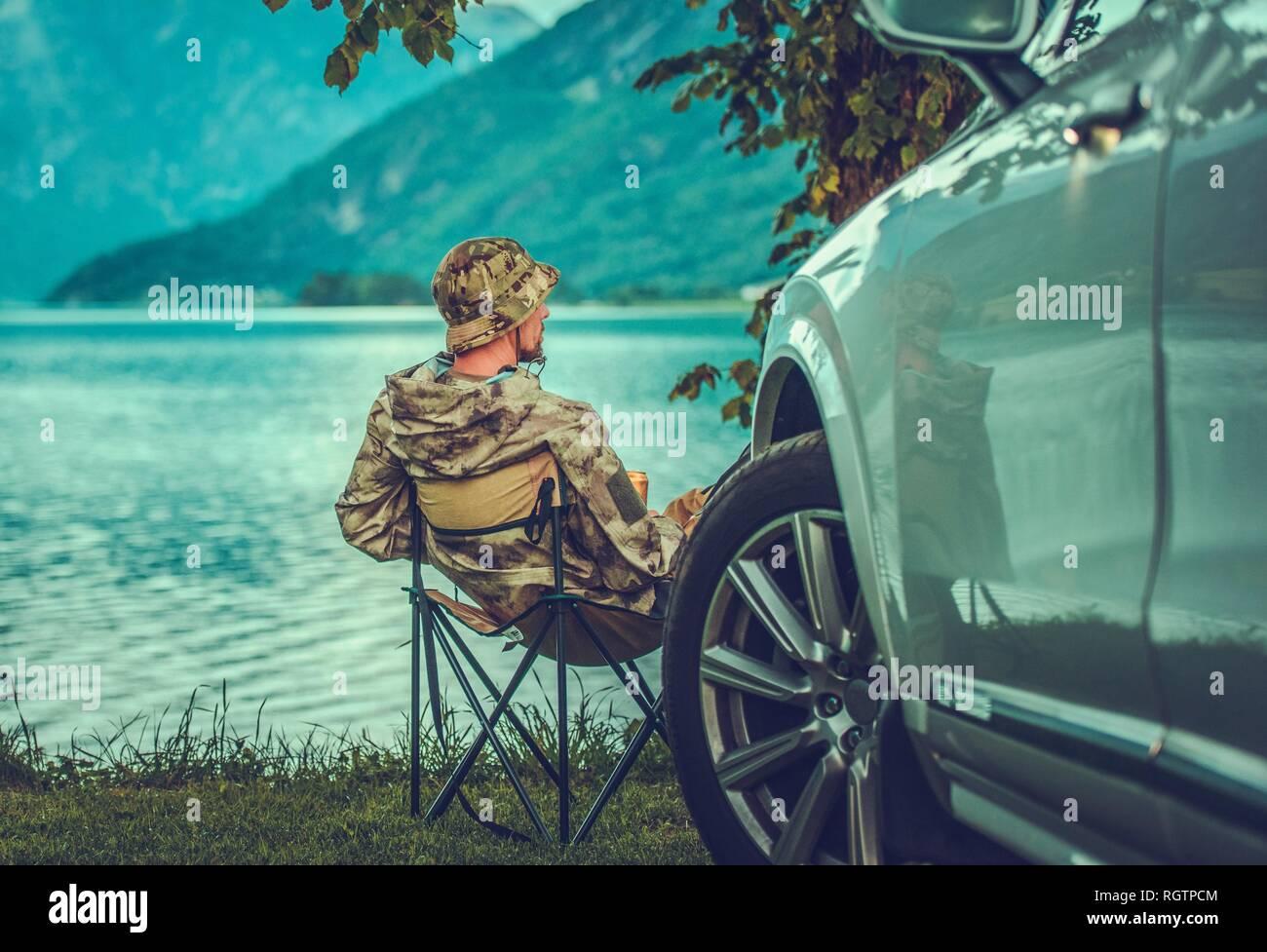Il weekend al lago. Uomini caucasici accelerando il suo tempo libero sulla riva del lago. Fuga in auto. Immagini Stock