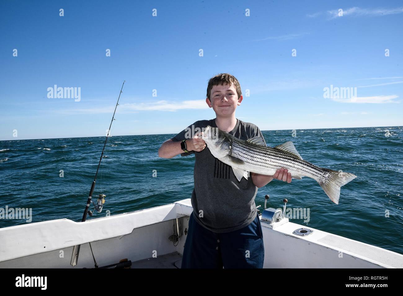 Orgoglioso ragazzo con pesce catturato in mare profondo escursione di pesca. Foto Stock