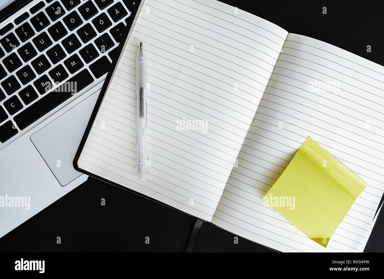 Blank aprire Appunti con bigliettino giallo accanto al computer portatile Immagini Stock