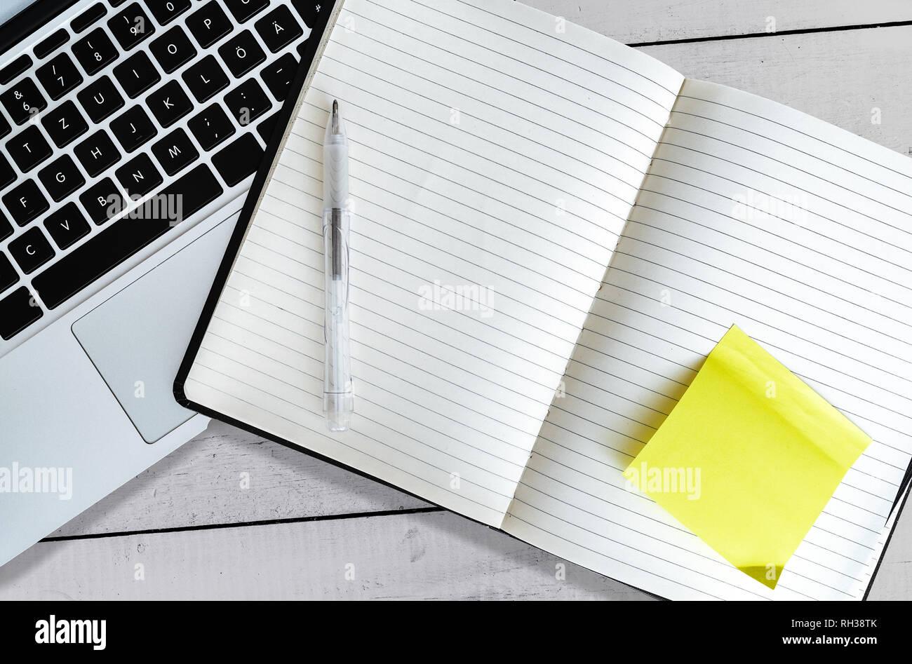 Blank aprire Appunti con bigliettino giallo accanto al laptop sul bianco rustico tavolo in legno Immagini Stock