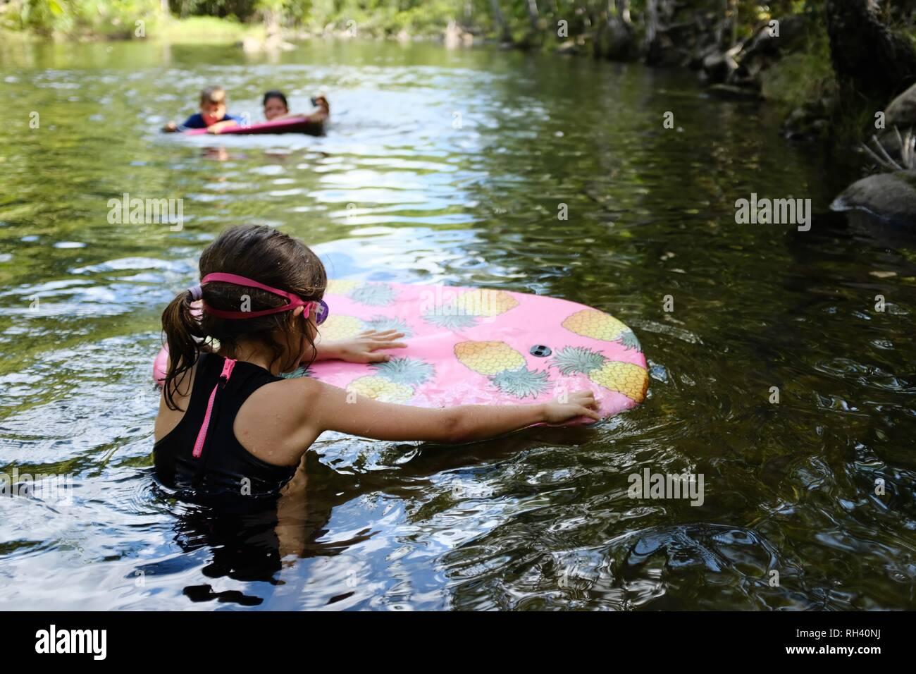 Ragazza giovane le piastre su un boogie board con la famiglia in background, Finch Hatton, Queensland 4756, Australia Foto Stock