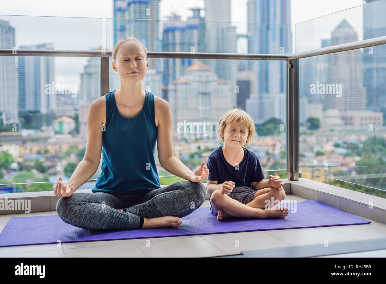 edc8edf2ae0f Madre e figlio sono la pratica dello yoga sul balcone sullo sfondo di una  grande città. Sport mom con kid facendo mattina work-out a casa. Mamma e  Bambino ...