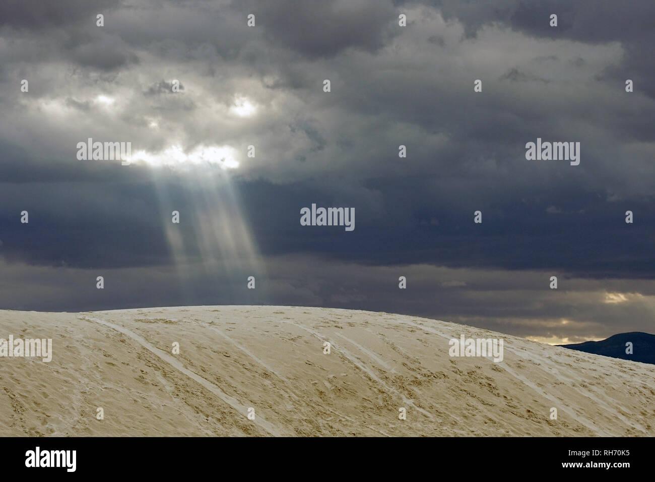 Raggi di sole rompere attraverso il cielo nuvoloso al White Sands, Nuovo Messico. Immagini Stock