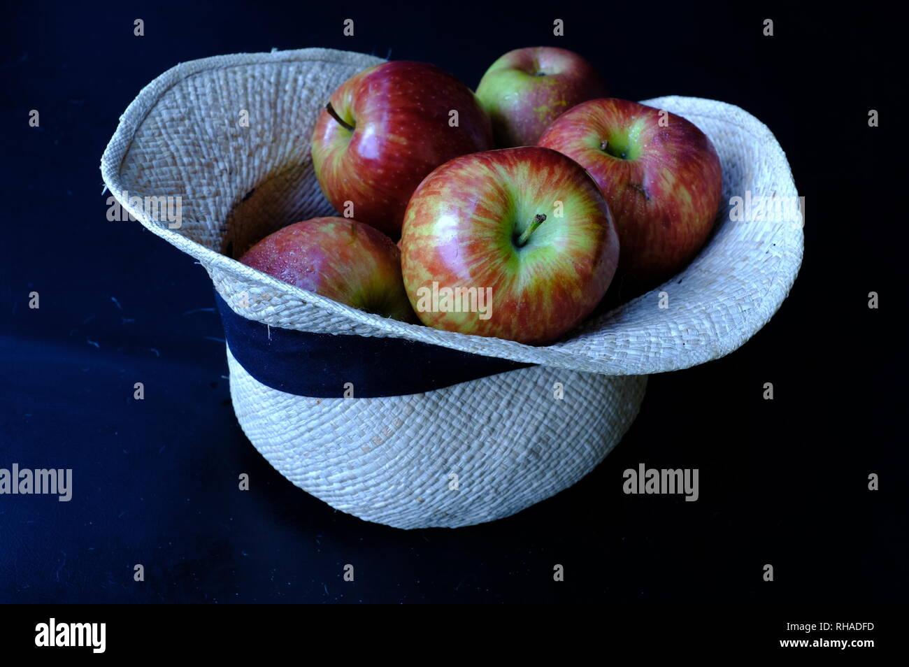 Primo Piano Di Carni Rosse Mele All Interno Di Una Bianca Cappello Di Paglia Su Uno Sfondo Nero Concetto Di Benessere E Salute Foto Stock Alamy
