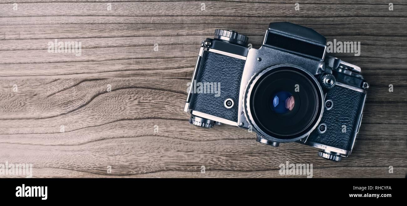 'Fotocamera retrò su sfondo di legno. Immagine panoramica con copia spazio. Immagini Stock