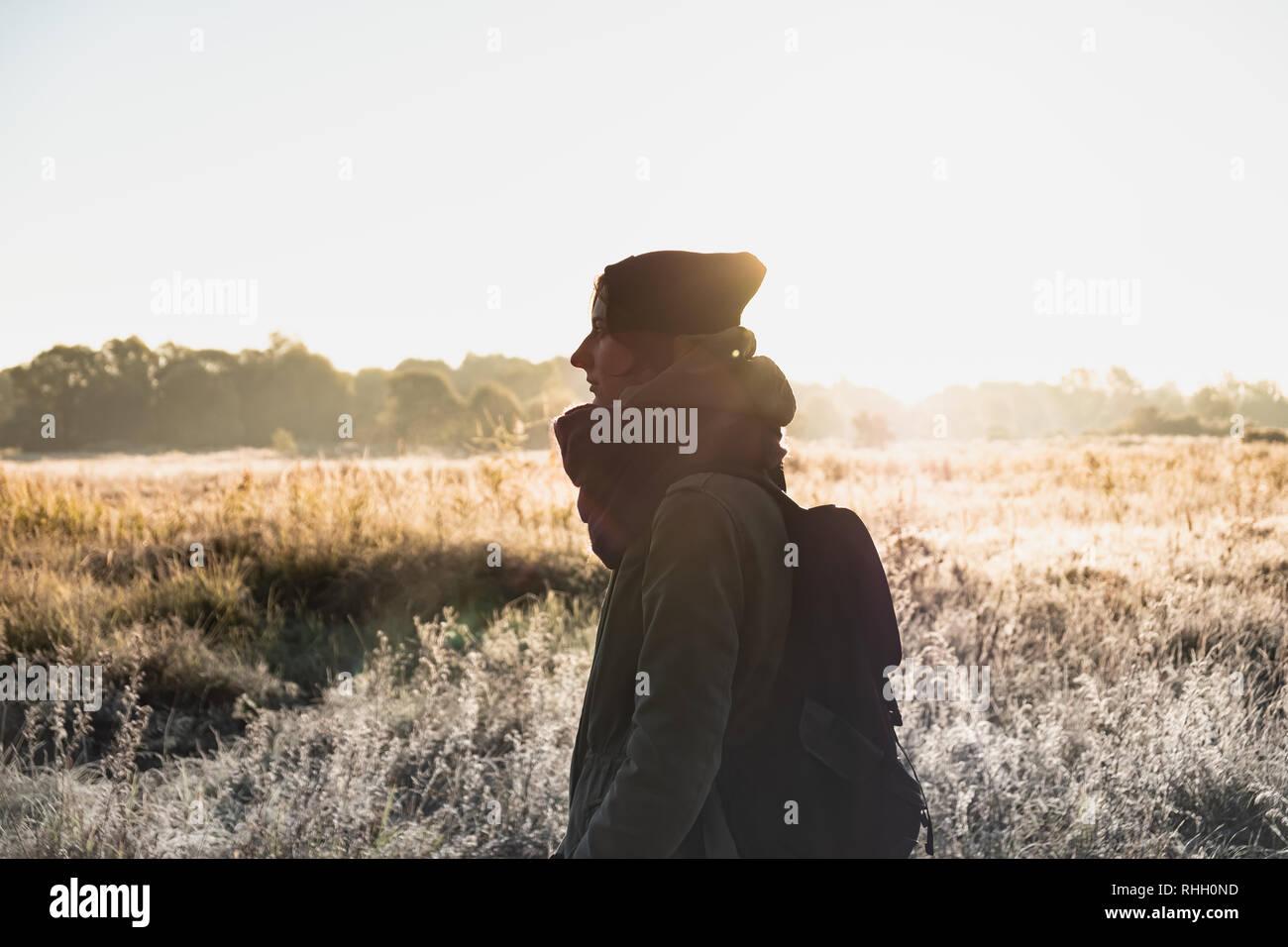 Backlit ritratto di donna bella sotto la luce diretta del sole. Persona di sesso femminile passeggiate all'aperto nella fredda mattina di sole in autunno Foto Stock