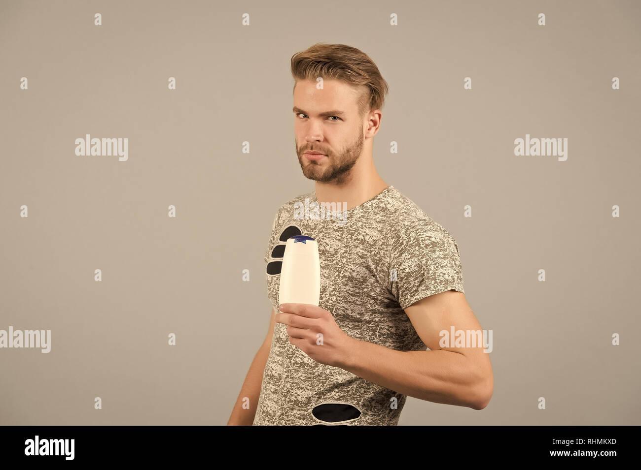 Uomo con shampoo o gel flacone in mano. Macho con i capelli alla moda b0f1b9d9aee4