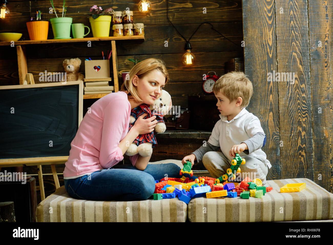 La gentilezza e il concetto di istruzione. La famiglia gioca con Teddy bear a casa. Mamma e Bambino gioca con il giocattolo morbido. Vivaio con lavagna su sfondo. Madre Immagini Stock
