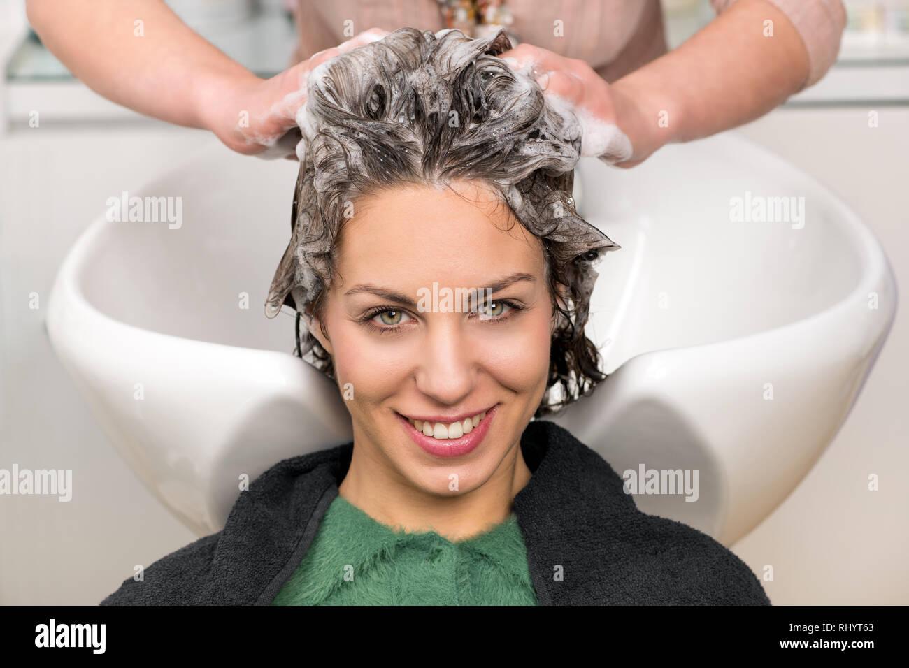Carino giovane ragazza con i capelli lavati con shampoo per le mani del  parrucchiere professionale al d7e1b57b8204