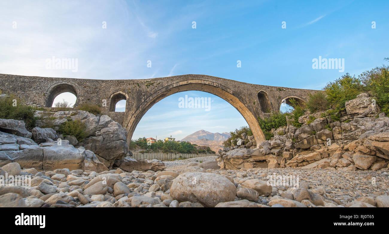 Il ponte di Mesi (Ura e Mesit) in MES, Albania, vicino a Scutari . Una vecchia pietra ponte ottomano - il più grande del paese. A secco fiume e montagna Immagini Stock