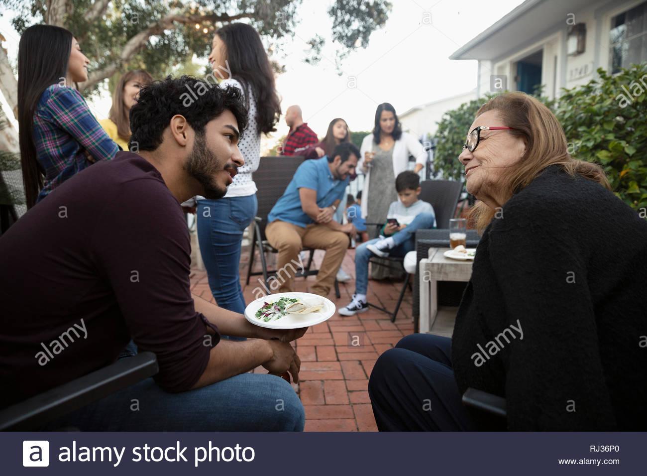 Latinx Nonna e nipote di parlare al barbecue di famiglia Immagini Stock