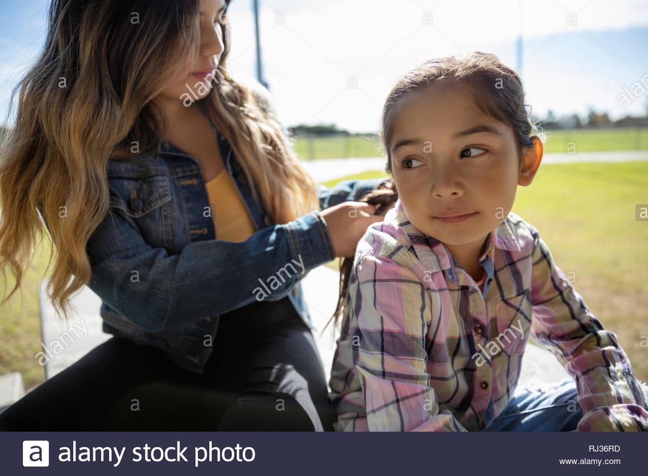 Ragazza Latinx trecciatura sorella s capelli Immagini Stock
