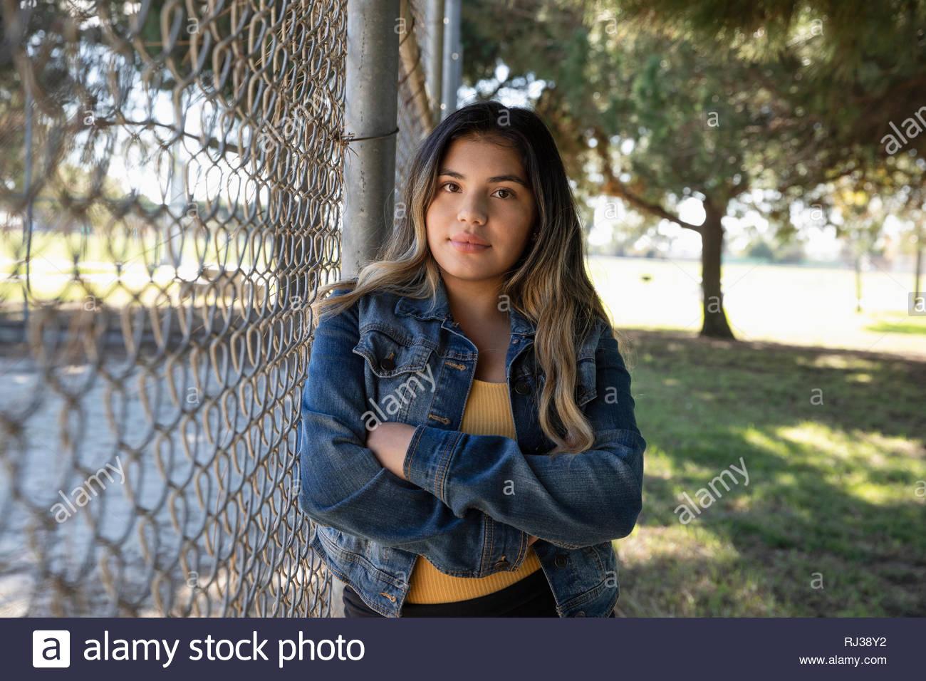 Ritratto fiducioso Latinx giovane donna in piedi alla recinzione del parco Immagini Stock
