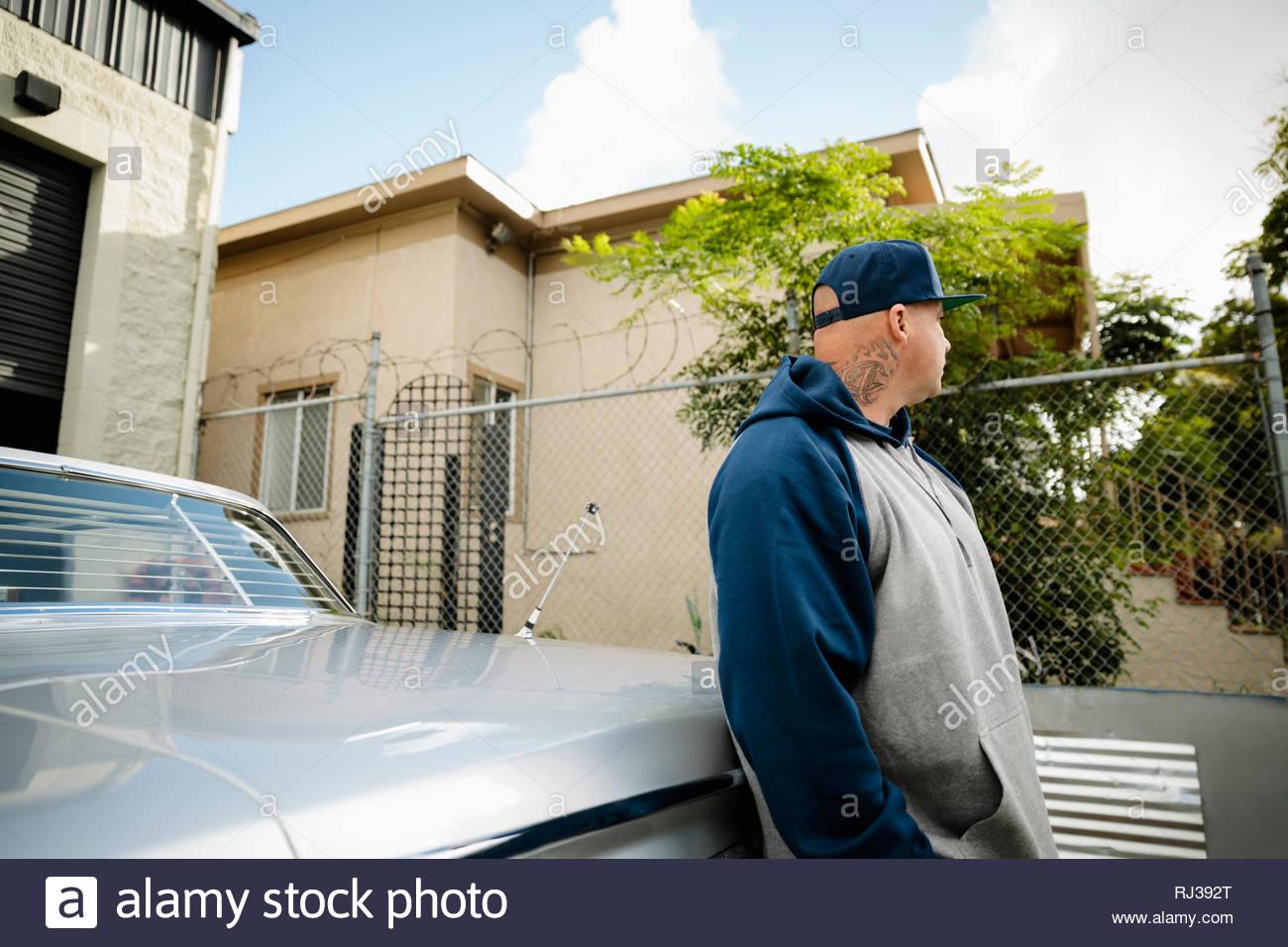 Latinx uomo appoggiato contro l'auto d'epoca Immagini Stock