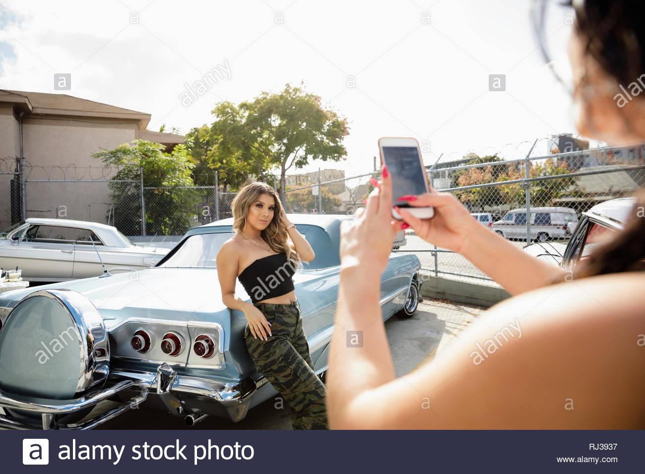 Latinx giovane donna in posa contro il pilota bassa auto d'epoca, nella soleggiata area di parcheggio Immagini Stock