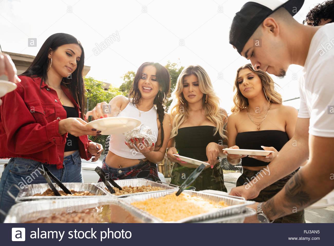 Latinx amici gustando un pranzo taco Immagini Stock