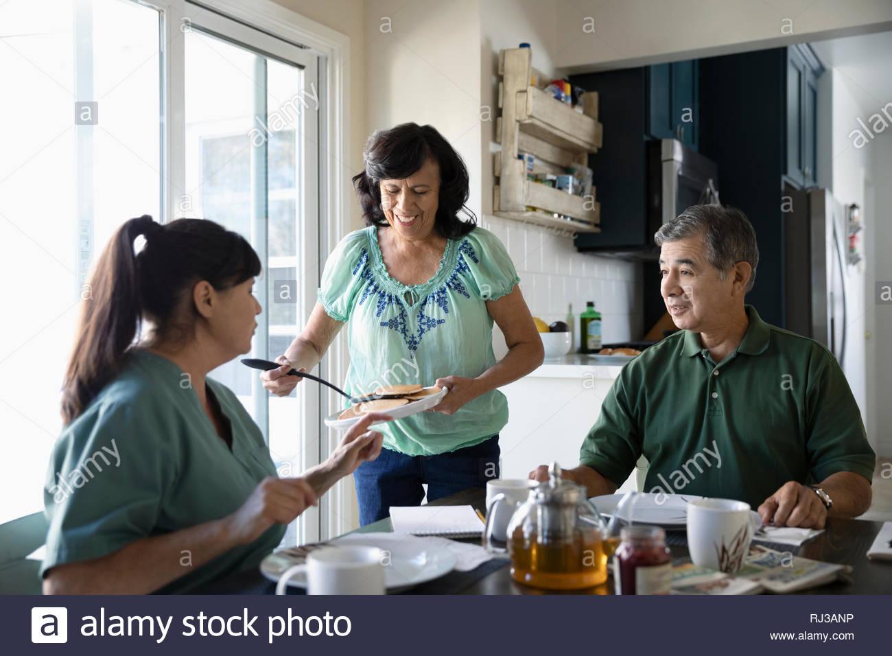 Senior Latinx donna che serve pancakes al marito e figlia al tavolo della cucina Foto Stock