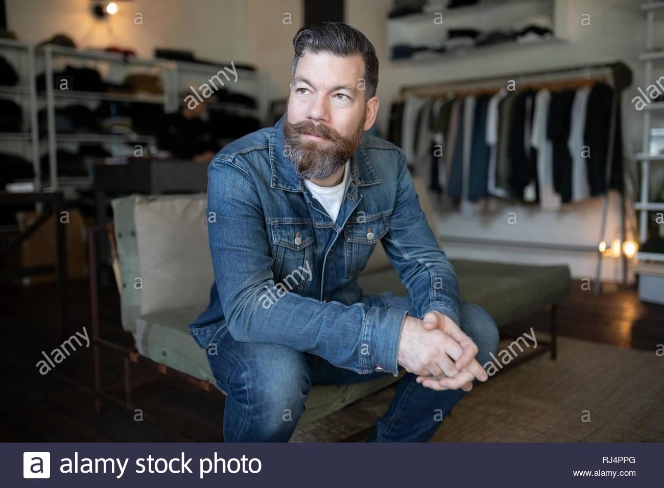 Fiducioso maschio proprietario di affari in seduta menswear negozio di abbigliamento Immagini Stock