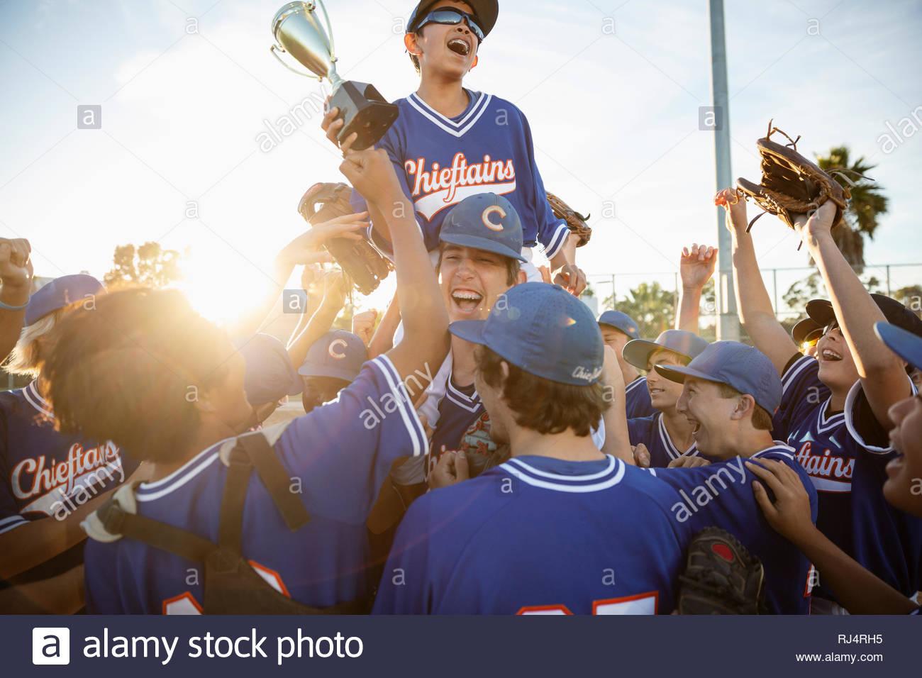 Emozionato squadra di baseball con trofeo celebrando Immagini Stock