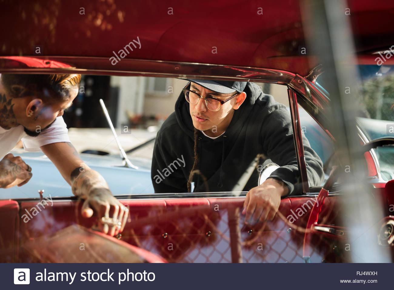 Latinx giovani uomini guardando all'auto d'epoca Immagini Stock