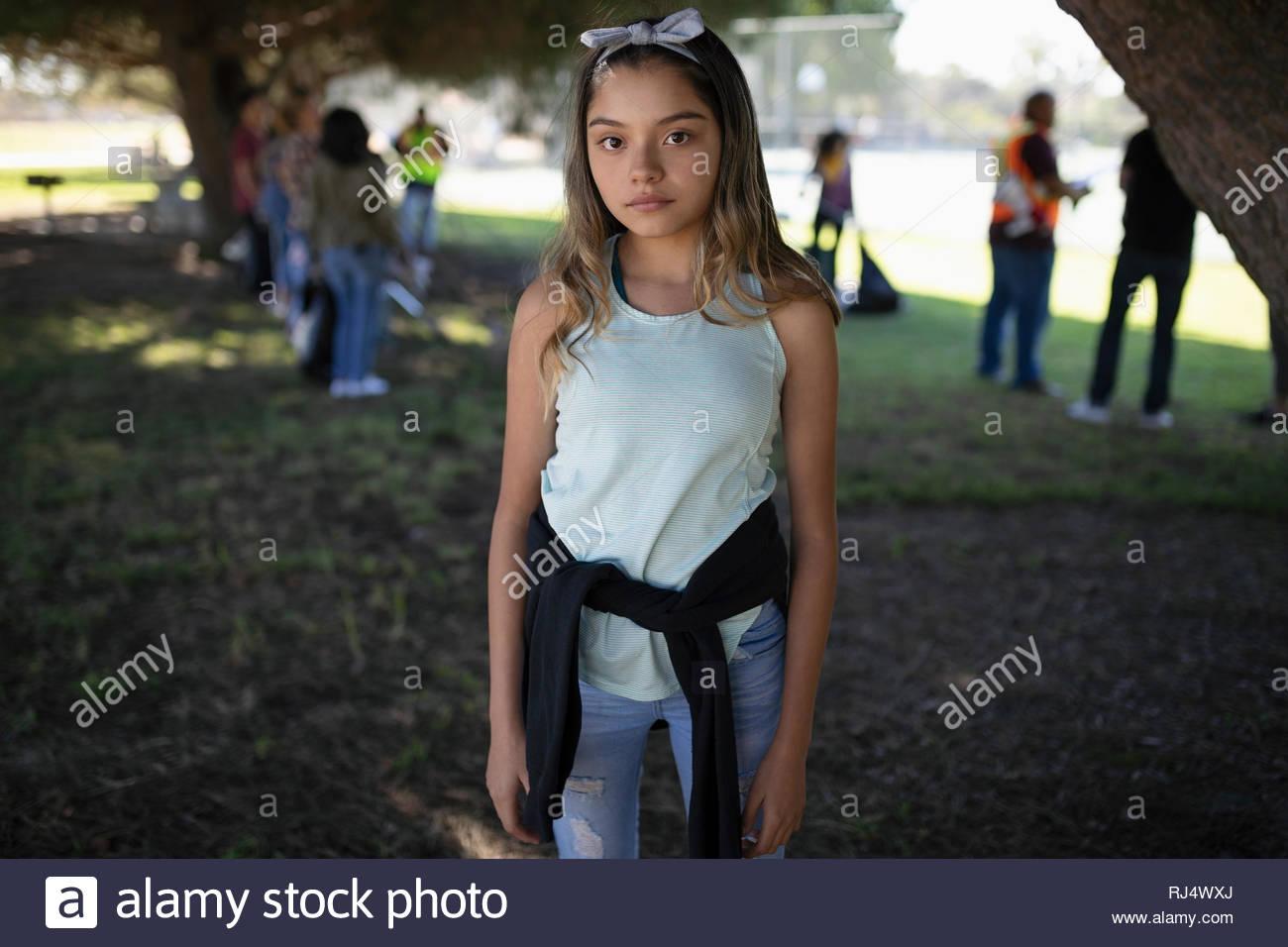 Ritratto fiducioso ragazza Latinx volontariato, parco di pulizia Immagini Stock