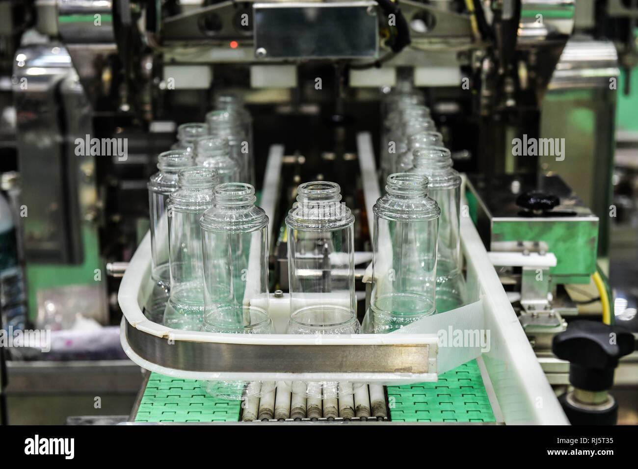 Cancellare le bottiglie di vetro trasferimento sul trasportatore automatizzato di sistemi di automazione industriale per il pacchetto Foto Stock