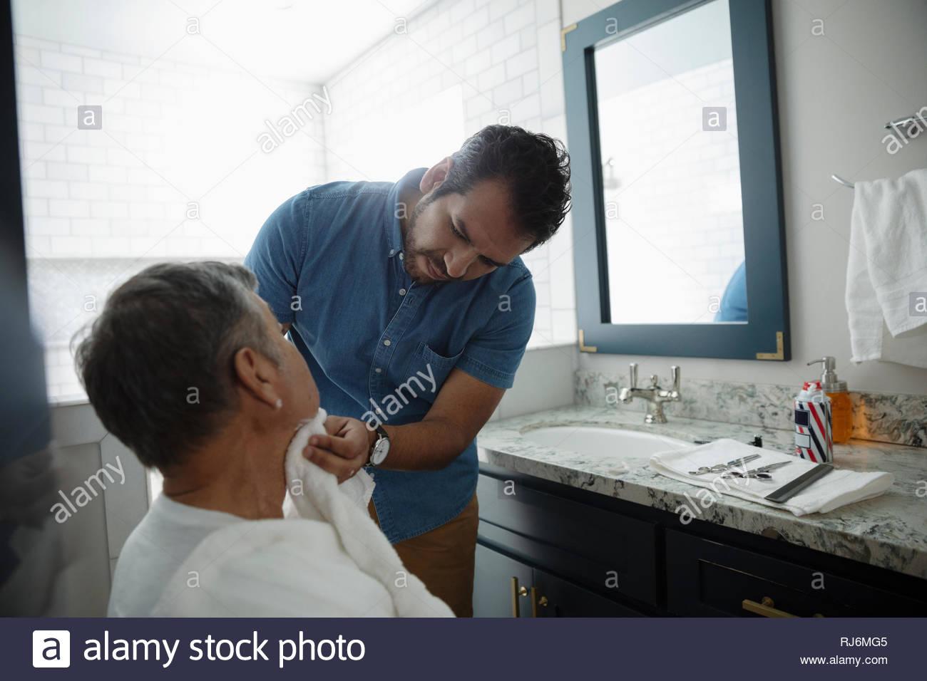 Latinx figlio di rasatura padre senior s volto nella stanza da bagno Immagini Stock