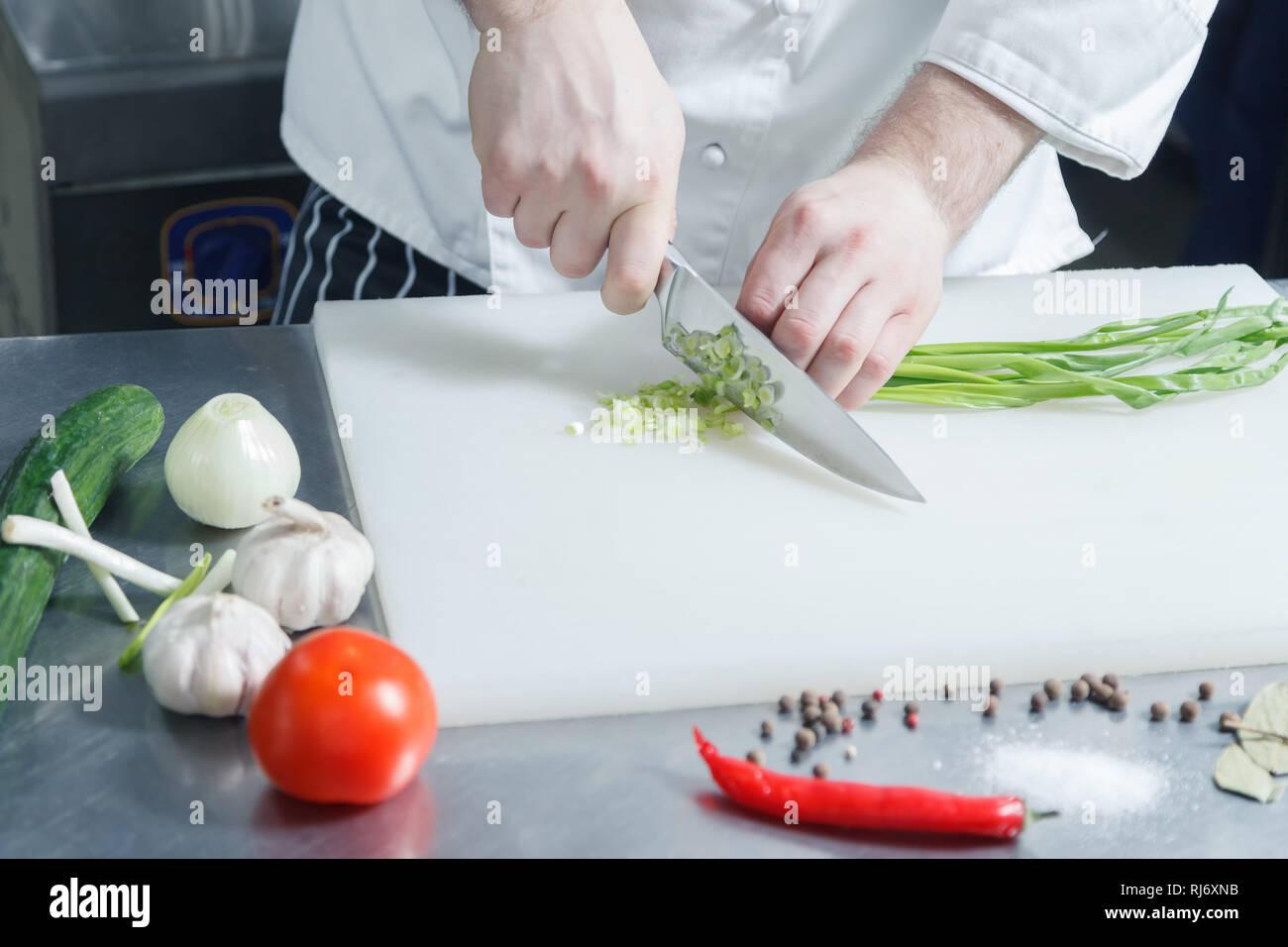 Tagliere Per Piano Cucina primo piano dello chef di cucina mani di cipolla verde per