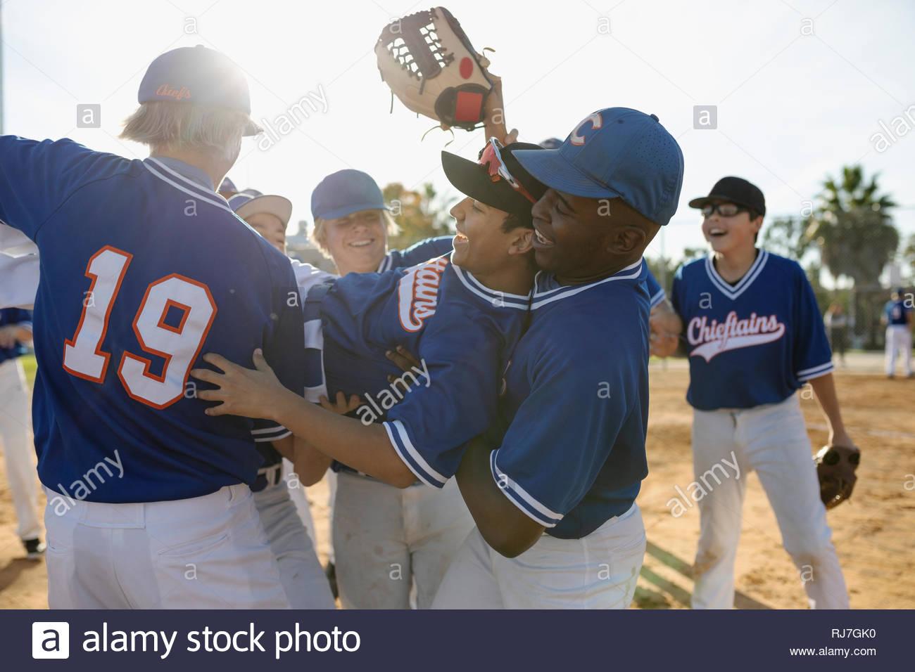 Felice squadra di baseball celebrando, portando giocatore di baseball Immagini Stock