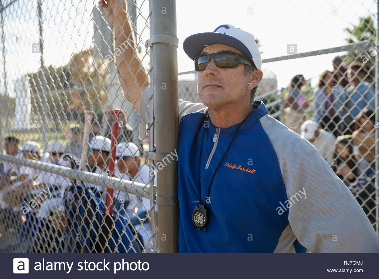 Focalizzato allenatore di baseball appoggiata sulla recinzione Immagini Stock