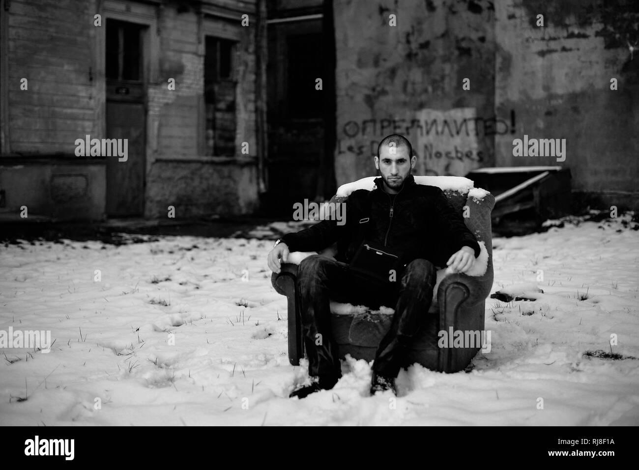 Ritratto in bianco e nero di un coraggioso ragazzo seduto sulla sedia  abbandonati per strada da c2c04dfad3c8