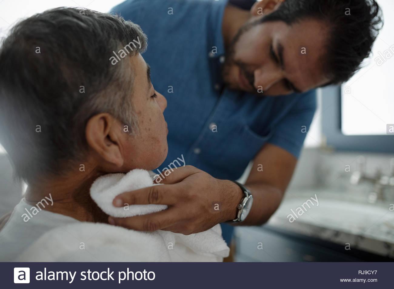 Figlio Latinx senior di rasatura padre faccia s Immagini Stock