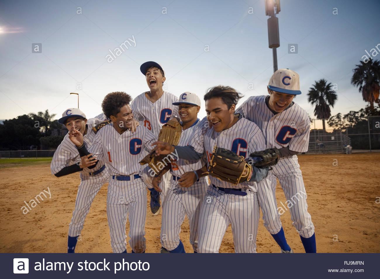 Emozionato squadra di baseball celebrando la vittoria sul campo di notte Immagini Stock