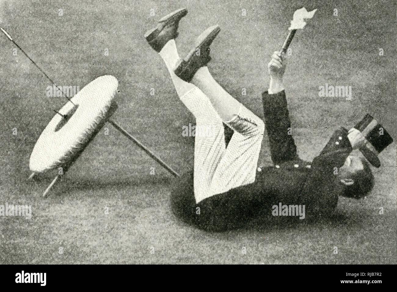L'uomo la segnalazione di una hit in inglese tiro con l'arco, gettandosi sulla sua schiena sul terreno e agitando un panno bianco attaccato ad un bastone corto e agitando le gambe all'aria. Immagini Stock