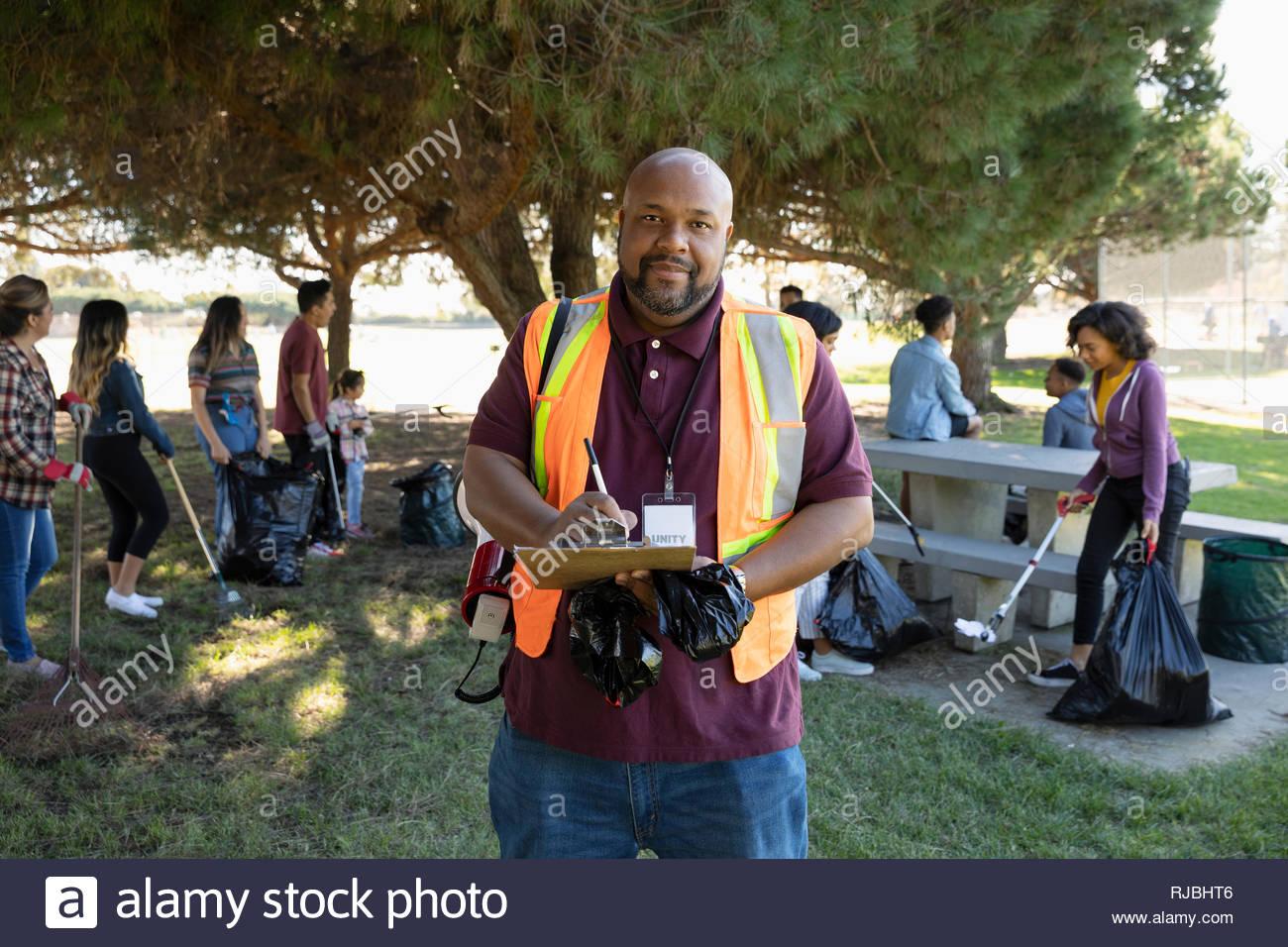 Ritratto fiducioso volontario con appunti parco di pulizia Immagini Stock