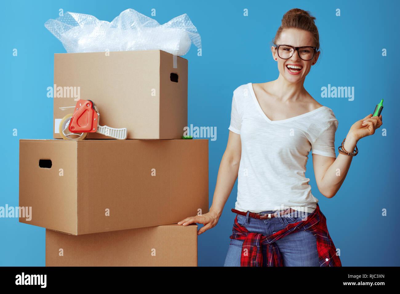 59e270f17569 Felice giovane donna in t-shirt bianco vicino alla scatola di cartone con un  marcatore