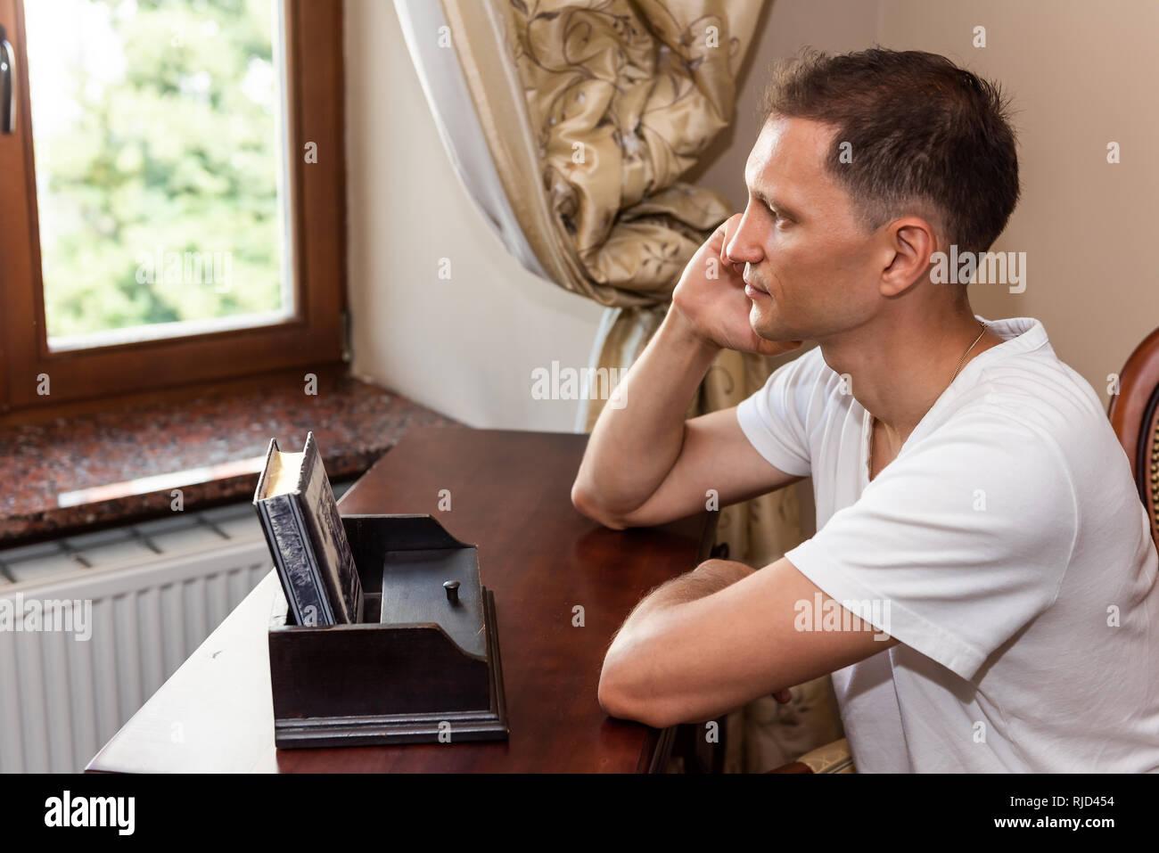Giovane uomo seduto su una sedia da rustico in legno vintage tavolo antico  e i ciechi della 52ad8f94e404