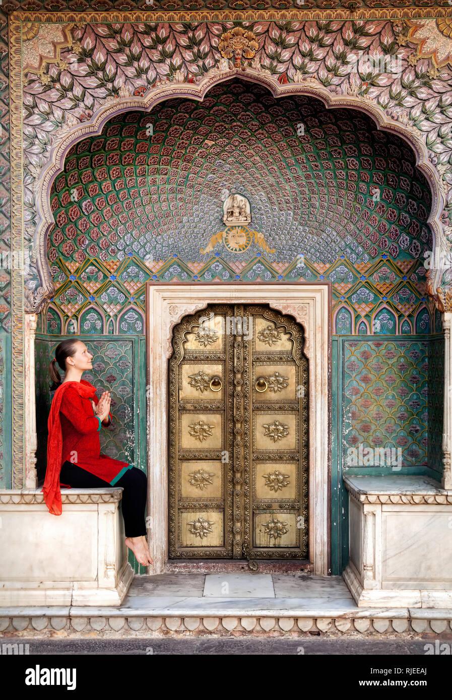 La donna in sciarpa rossa seduta vicino Lotus gate nel palazzo di città di Jaipur, Rajasthan, India Immagini Stock