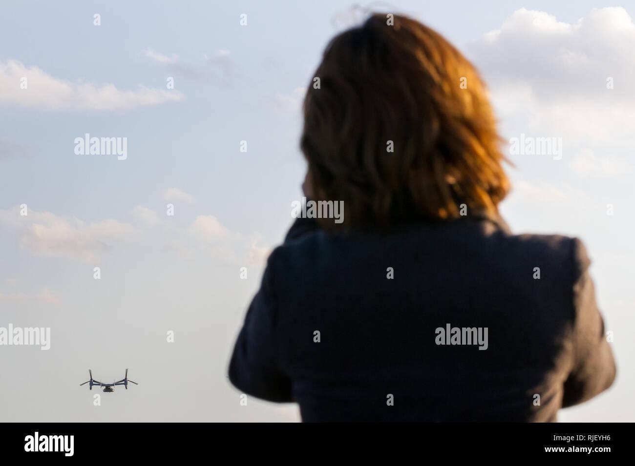 Una donna giapponese orologi il controverso Bell Boeing V22 Osprey tilt-rotore in aereo con la US Navy, tenendo fuori dalla Naval Air Facility di Atsugi in Y Immagini Stock