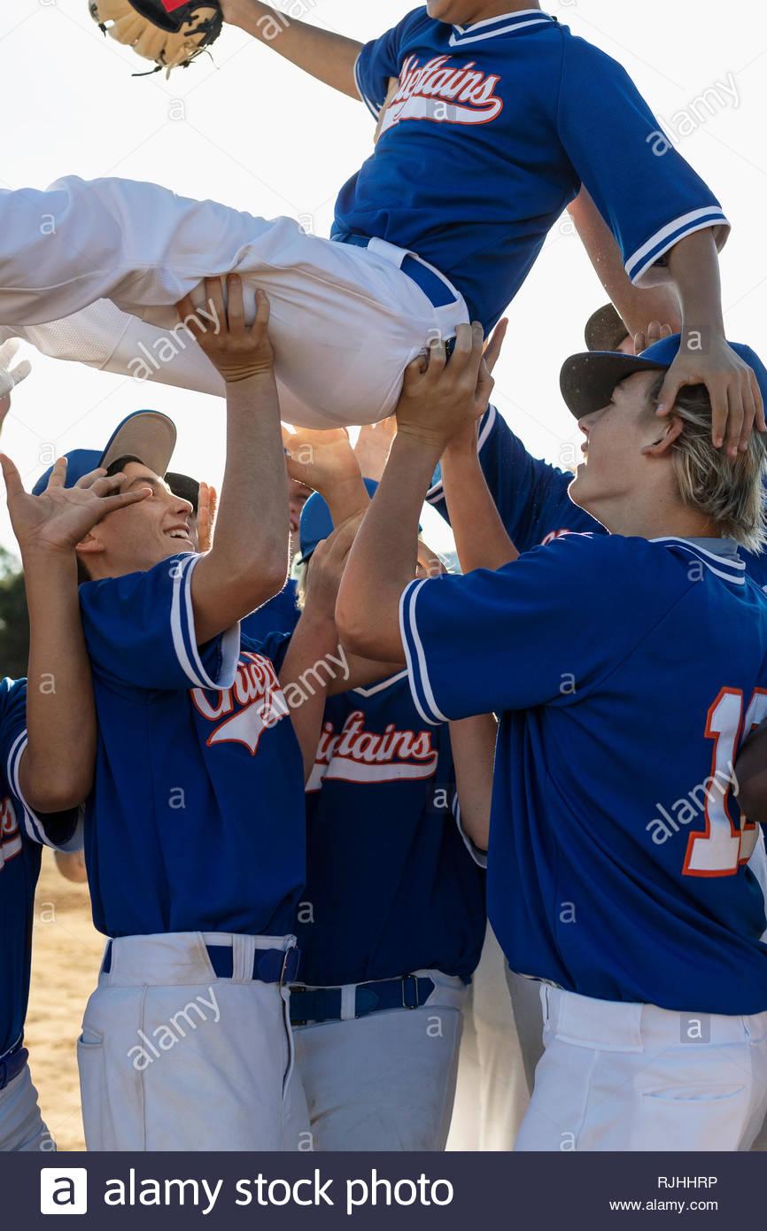 Emozionato i giocatori di baseball celebrando, portando il suo compagno di squadra tettuccio Immagini Stock