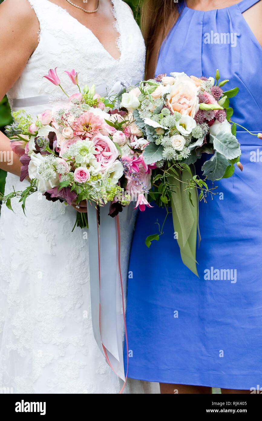 fa379a19063a Sposa e damigella tenendo le loro nozze bouquet di fiori con il grigio e  verde ai