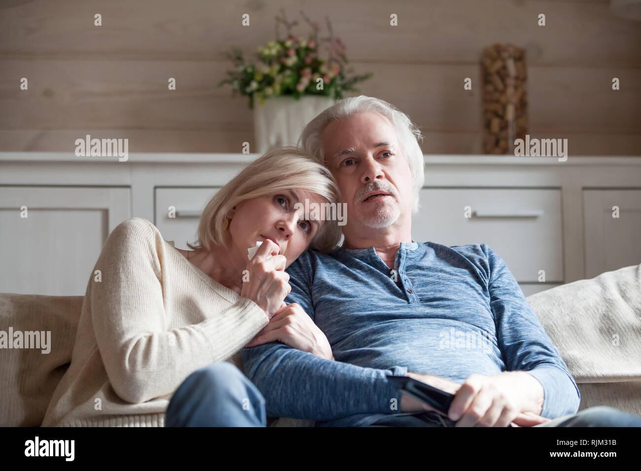 La vecchiaia coniugi seduti sul divano guardando film thriller Immagini Stock