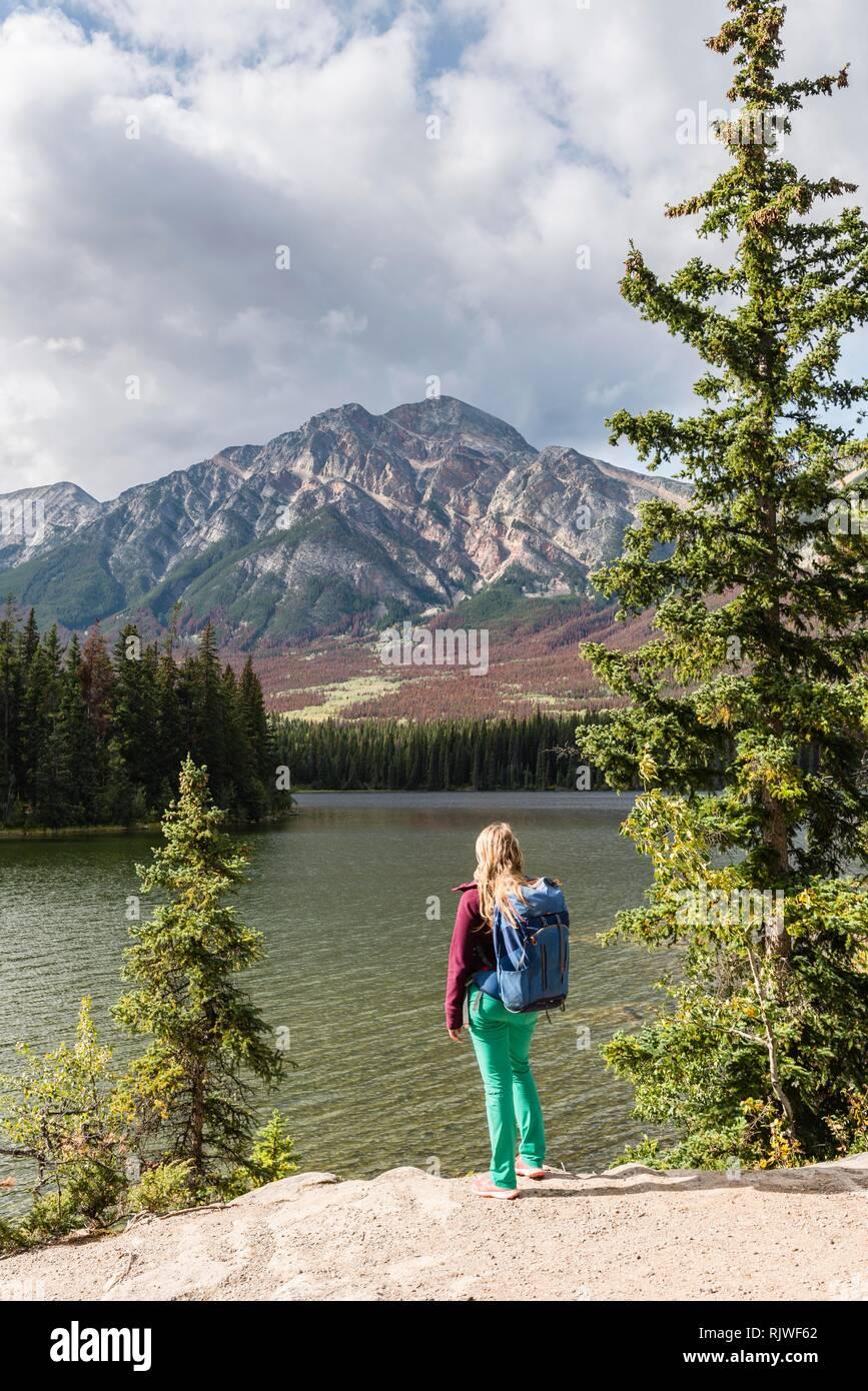 Escursionista femmina sorge sulla riva del Lago, Lago Piramide, torna montagne, piramide, di montagna del Parco Nazionale di Jasper National Park Immagini Stock